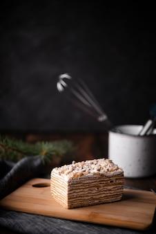 Kuchen auf schneidebrett mit küchengeräten