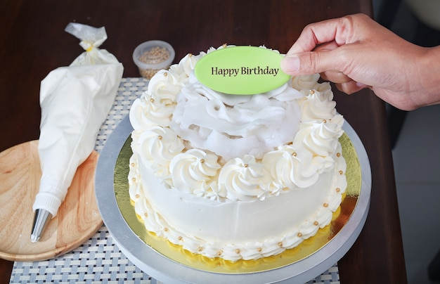 Kuchen auf stand mit der hand, die aufkleberwort hält