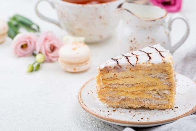 Kuchen auf teller mit macarons und rosen