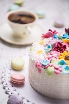 Kuchen aus marzipanblüten, makronen und einer tasse schwarzem kaffee.