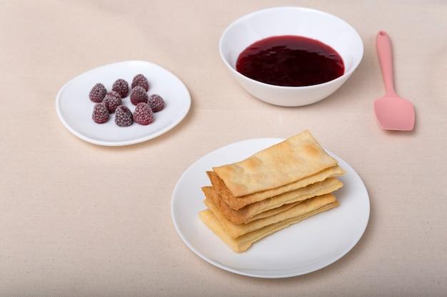 Kuchen, beeren und obstmarmelade auf untertassen. zutaten für die herstellung von obstkuchen.