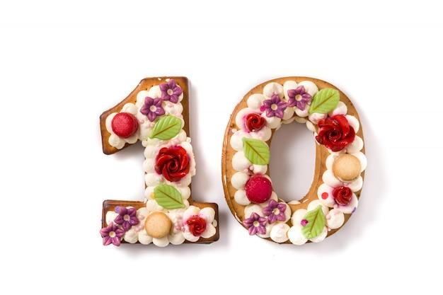 Kuchen der nr. zehn verziert mit den blumen und macarons lokalisiert auf weißer oberfläche.