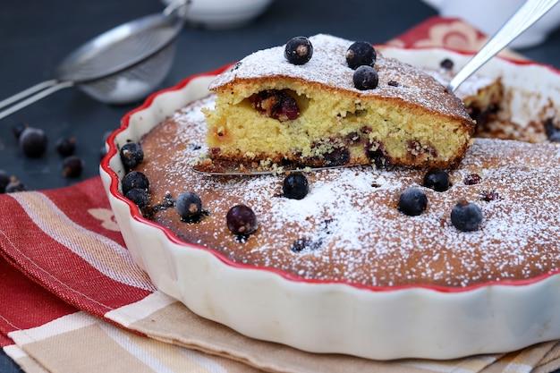 Kuchen der schwarzen johannisbeere befindet sich in einer keramischen form mit einem geschnittenen stück kuchen