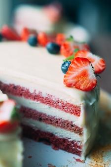 Kuchen des selektiven makrofokus mit beeren und weißer glasur