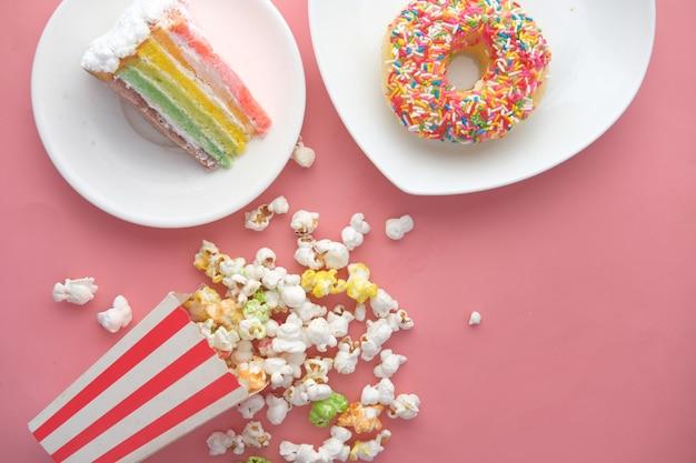Kuchen donuts und popcorn auf rosa