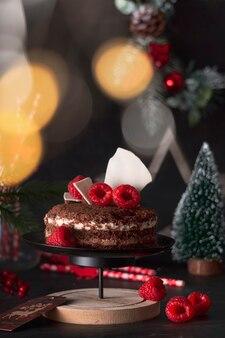 Kuchen drei pralinen in einer neujahrs-weihnachtsdekoration mit himbeeren