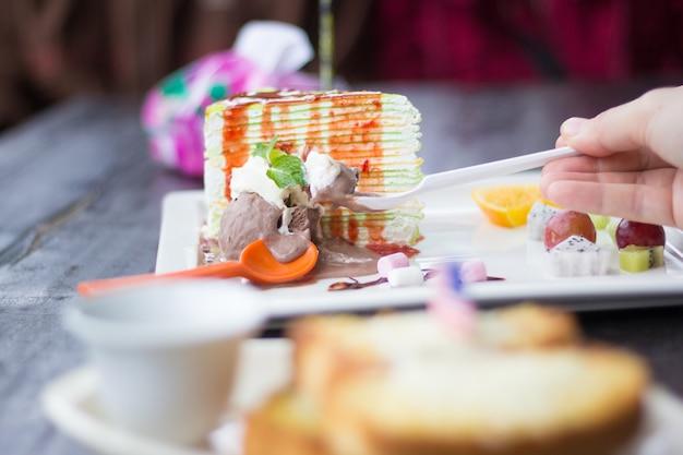 Kuchen-eiscreme-köstlicher regenbogenkuchen, hände mit stück kuchen