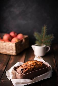 Kuchen in der pfanne mit korb von äpfeln