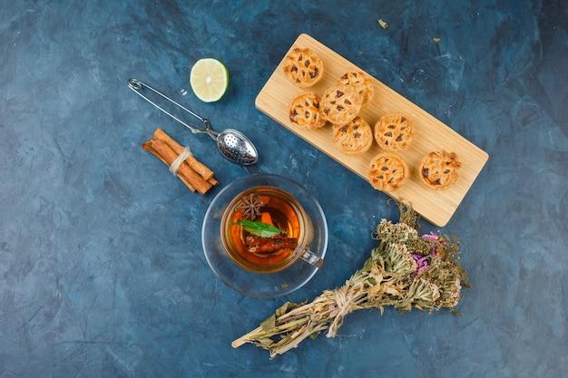 Kuchen in einem schneidebrett mit einer tasse tee, zimt und einem teesieb