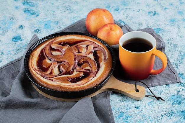 Kuchen in einer schwarzen pfanne mit pfirsich und einer tasse tee.
