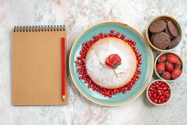 Kuchen kekse kuchen mit erdbeeren neben dem bleistiftnotizbuch