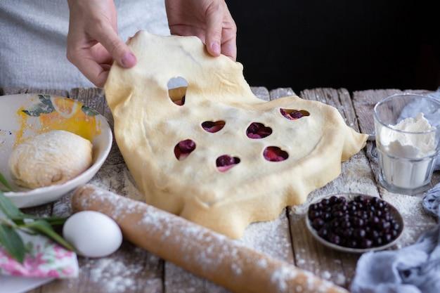 Kuchen kochen. hände verteilen den teig auf dem kuchen. geschlossener kuchen. der prozess der herstellung eines kuchens. backen zu hause. mama backt. bissform
