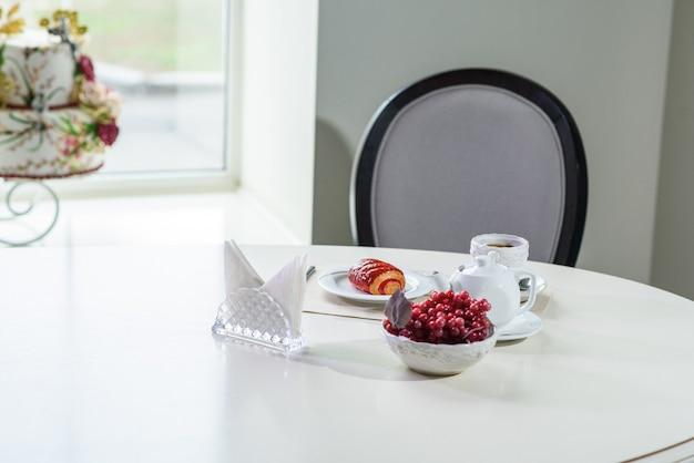 Kuchen mit beeren und schwarzem tee auf dem tisch in einem gemütlichen café