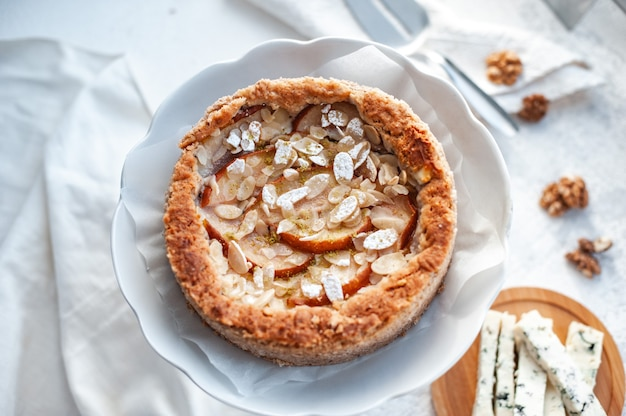 Kuchen mit dor blauschimmelkäse, birnen und mandeln, ganz rund auf einem teller auf einem weißen tisch.