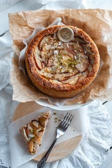 Kuchen mit dor blauschimmelkäse, birnen und mandeln, ganz rund auf einem teller auf einem weißen tisch