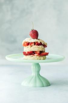 Kuchen mit erdbeeren auf blaugrünem keramikkuchenständer