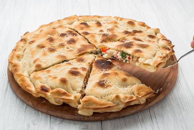 Kuchen mit fleisch, gemüse und käse auf einer holzoberfläche