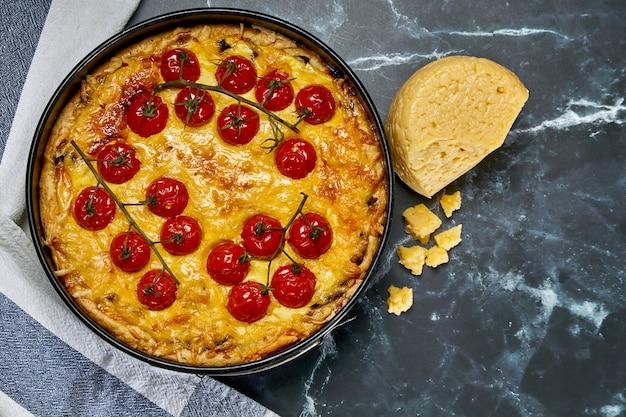 Kuchen mit gebackenen ganzen kirschtomaten auf einem ast und huhn, gefüllt mit sahne, käse und eiern