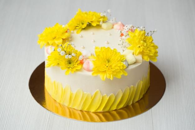 Kuchen mit gelben flecken, gelben chrysanthemen und baiser