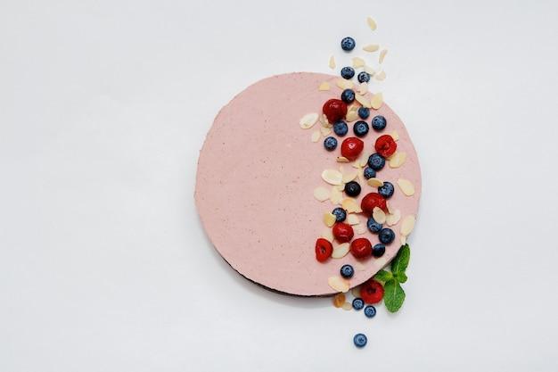 Kuchen mit geschlagener rosa sahne, blaubeeren, brombeere und himbeere auf weißem hintergrund. ansicht von oben. bild für ein menü oder einen süßwarenkatalog.