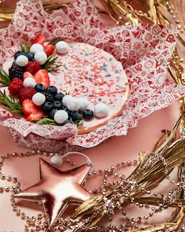 Kuchen mit geschlagener rosa sahne, frischen erdbeeren, blaubeeren, brombeeren und himbeeren auf rosa hintergrund. bild für ein menü oder einen süßwarenkatalog.