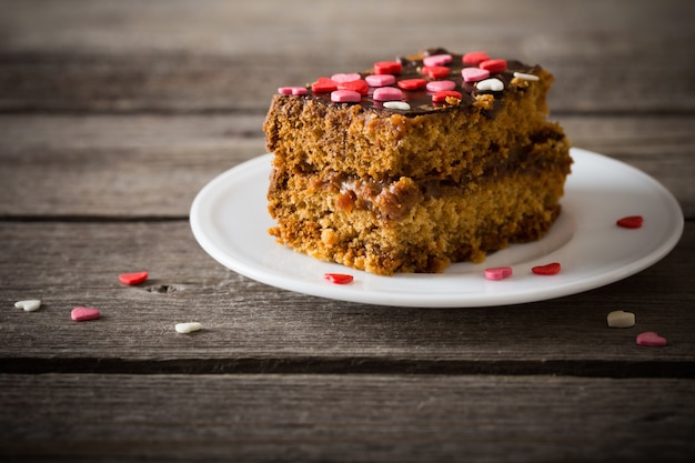 Kuchen mit herzen auf hölzernem hintergrund