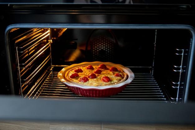 Kuchen mit hühnchen und tomaten liegt auf einem backblech im ofen.