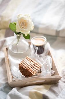 Kuchen mit kaffee und blume im tablett auf dem bett