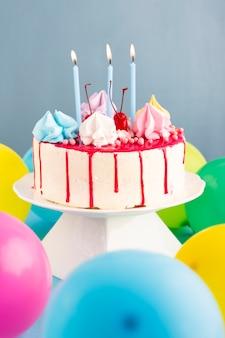 Kuchen mit kerzen und luftballons
