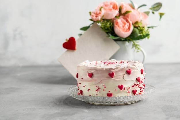 Kuchen mit kleinen herzen und buntem besprüht auf einer platte mit kaffee.