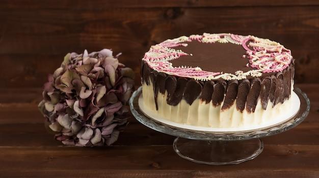 Kuchen mit mehendi-mustern auf dem glasständer. holzhintergrund.