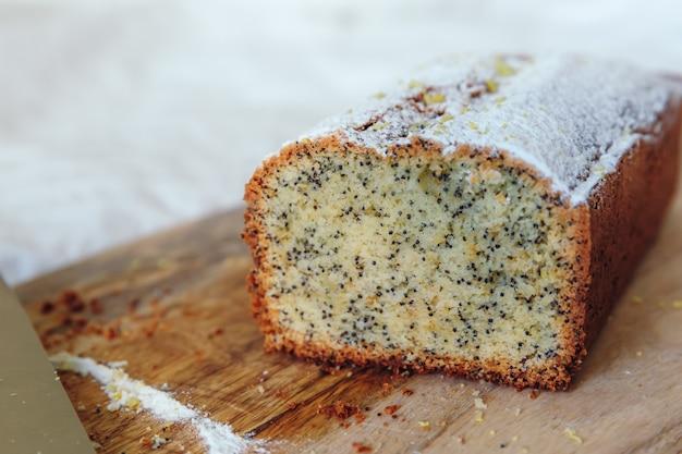 Kuchen mit mohn und zitronenschale, bestreut mit puderzucker. cupcake mit zitrone auf einem holzbrett.