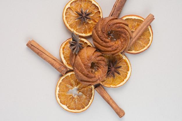 Kuchen mit orangenscheiben und zimt auf weißer oberfläche
