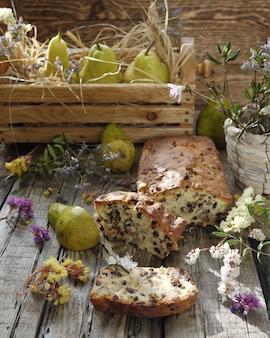 Kuchen mit rosinen und birnen auf holztisch im rustikalen stil