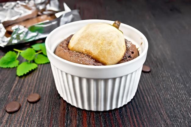Kuchen mit schokolade und birne in einer weißen schüssel, minze auf dem hintergrund dunkler holzplanken