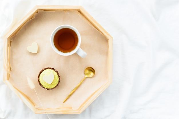 Kuchen mit schokoladenherz und einer tasse tee auf einem tablett auf einem weißen bett