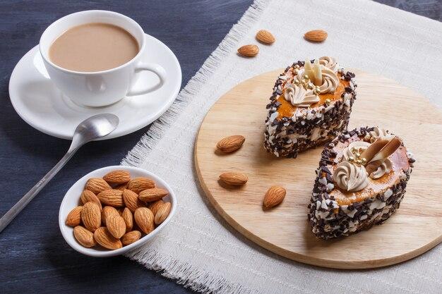 Kuchen mit schokoladensplittern und sahnedekorationen auf hölzernem brett auf schwarzem hölzernem.