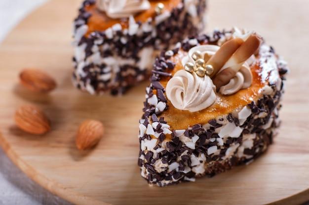 Kuchen mit schokoladensplittern und sahnedekorationen auf hölzernem brett auf weiß.