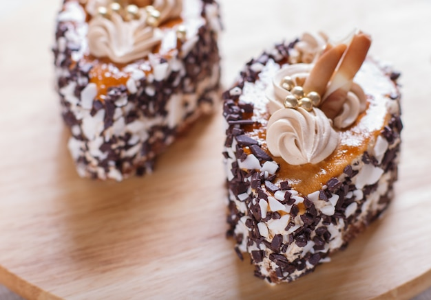 Kuchen mit schokoladensplittern und sahnedekorationen auf hölzernem brett