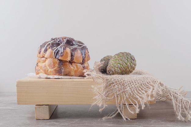 Kuchen mit schokoladenüberzug und zwei tannenzapfen auf einem brett auf marmor