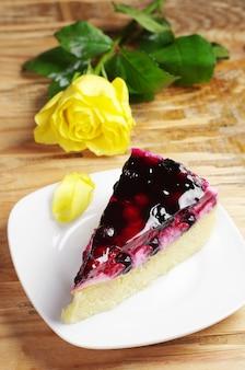 Kuchen mit schwarzer johannisbeere und gelber rose auf altem holztisch