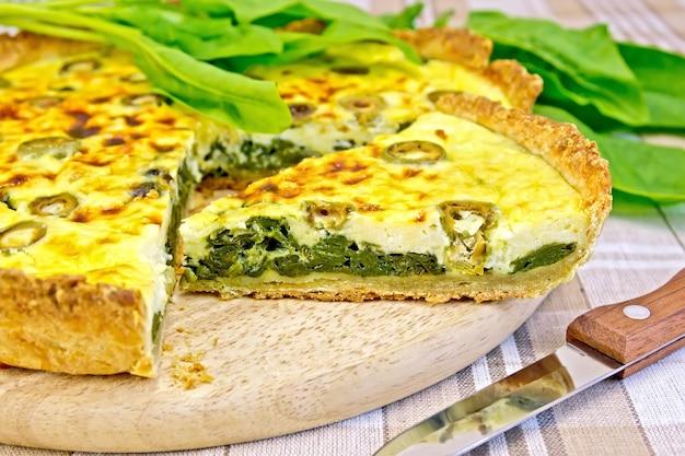 Kuchen mit spinat, käse und oliven auf einem runden brett, spinatblättern, messer auf leinentischdecken im hintergrund
