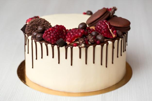 Kuchen mit weißer sahne, schokoladentropfen, granatapfel, nüssen und schokoladendekor