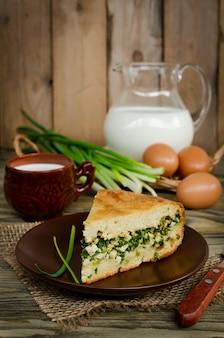 Kuchen mit zwiebeln und eiern auf dem holztisch