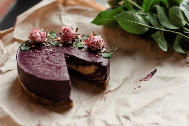 Kuchen ohne ein stück. lila kuchen und blumen. kuchen mit blumendekor. ein wunderschönes natürliches dessert.