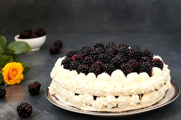 Kuchen pavlova mit brombeeren und schlagsahne auf einer dunklen oberfläche