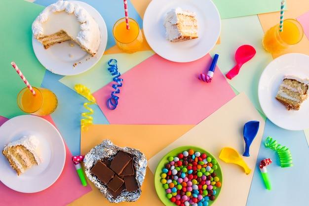 Kuchen, süßigkeiten, schokolade, pfeifen, luftschlangen, luftballons, saft auf feiertagstisch.