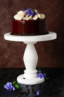 Kuchen tiramisu in schokoladenglasur mit mascarpone-creme und dekoriert mit kaffeebohnen und veilchen