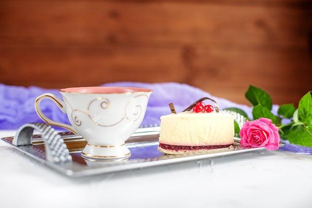 Kuchen und heißer tee auf einem tablett auf einem hölzernen hintergrund.