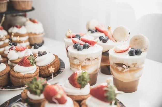 Kuchen und muffins mit sahne und beeren. süßigkeiten, bonbons, buffet. dessert tisch. partyempfang, dekoriert im restaurant. schokoriegel